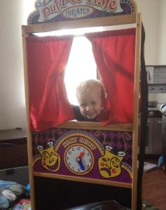 Playing with his new puppet theater- a gift from a friend!
